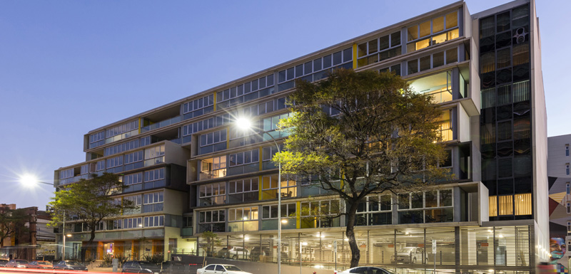 exterior up-shot of iStay Precinct hotel in Adelaide city at dusk with lights on and car parking on street