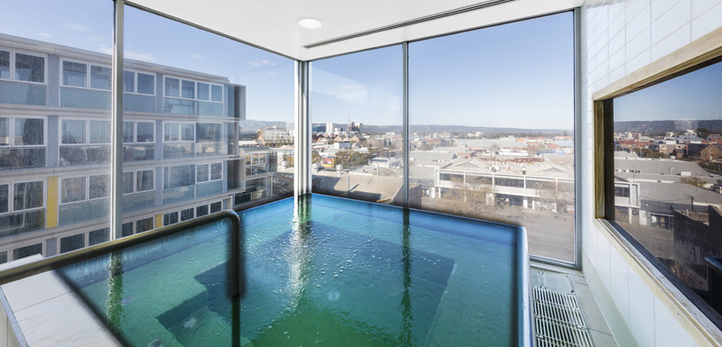 jacuzzi spa bath with large glass windows and views of Adelaide city at iStay Precinct hotel