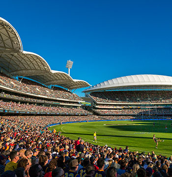 AFL game at Adelaide Oval with big crowd cheering and blue summer sky in background