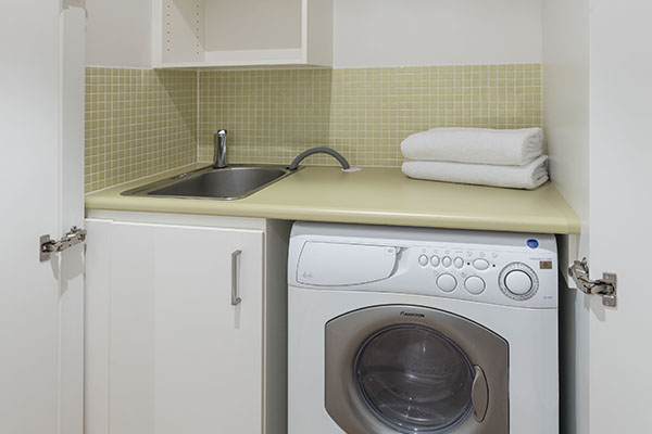 washing machine in laundry room of air conditioned 1 bedroom apartment at Oaks Liberty Towers hotel in Glenelg
