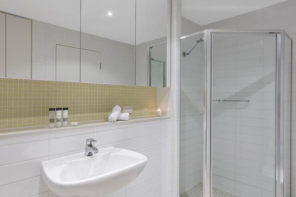 large shower, toilet and sink in en suite bathroom of 2 bedroom hotel apartment near Glenelg beach, South Australia