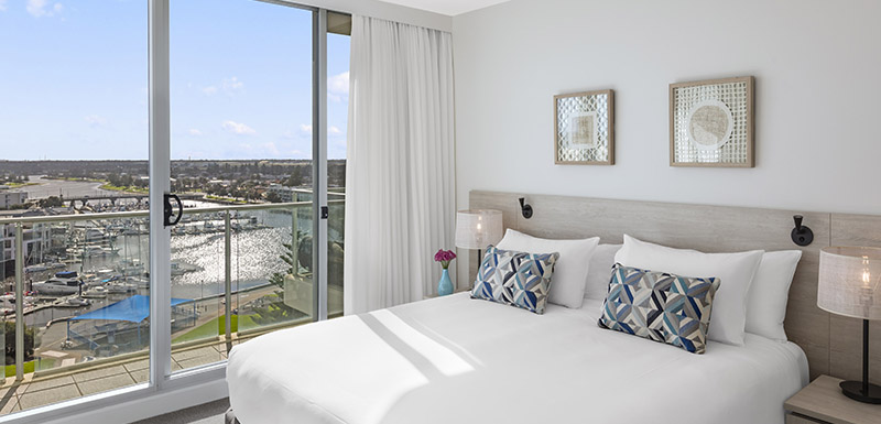 interior of master bedroom with large bed, air conditioning and private balcony with beautiful views of ocean in Glenelg, South Australia