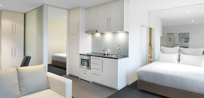 spacious open plan studio apartment with double bed, air conditioning, en suite bathroom and kitchenette with microwave, toaster and kettle at Oaks on Collins hotel in Melbourne CBD