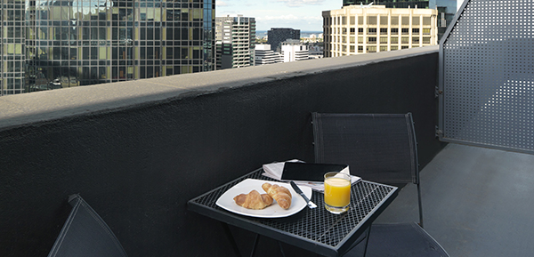 vegetarian breakfast and freshly squeezed orange juice in glass on table on private balcony of studio apartment with views of Melbourne city at Oaks on Collins hotel