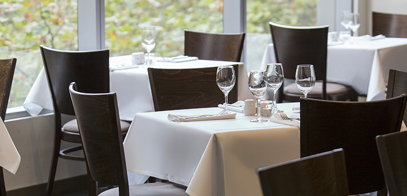table setting with cutlery, wine glasses and chairs next to window at 1st Floor Restaurant on 480 Collins St in Melbourne city, Victoria, Australia