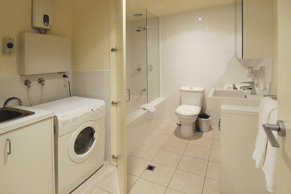 en suite bathroom with clothes washing machine and dryer in laundry room of 3 Bedroom Apartment near Flinders Street Railway Station in Melbourne, Victoria, Australia