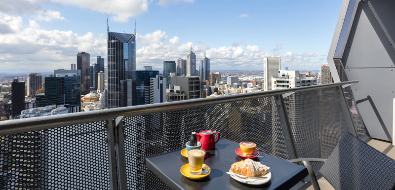 tea cups, coffee mug and crumpets on table on private balcony of serviced apartments in Melbourne at Oaks On William hotel in Melbourne city, Victoria, Australia