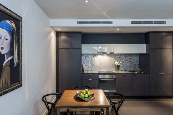 kitchen with oven, microwave, kettle for tea and coffee, cutlery and dining table with vegetarian food in 2 Bedroom Executive apartment in Melbourne CBD, Victoria, Australia