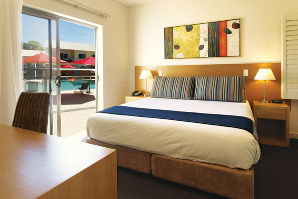 large, comfortable double bed with clean sheets next to desk for corporate travellers to do work while visiting Broome, WA
