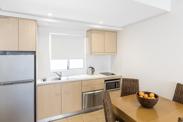 kitchen with modern appliances including microwave, big refrigerator, freezer and kettle in 1 bedroom apartment at Oaks Broome hotel, Western Australia