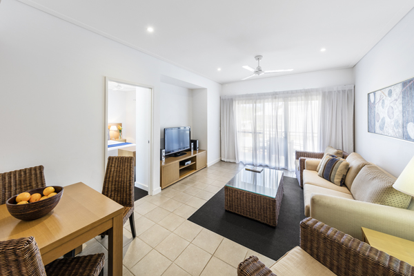spacious living room with Foxtel on TV, air conditioning, ceiling fan and dining table in 1 bedroom hotel apartment in Western Australia
