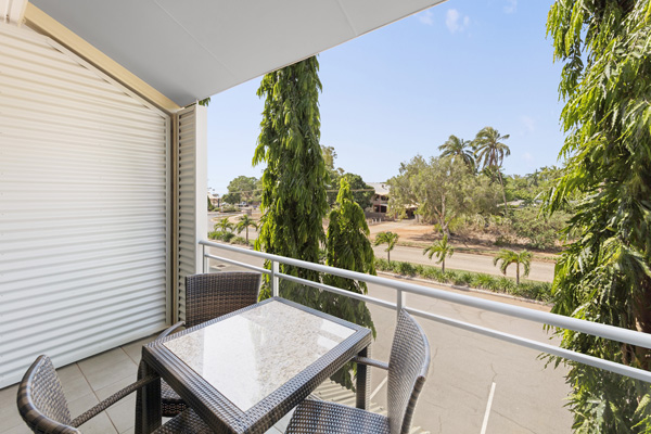 table and chairs on private balcony of hotel room at Oaks Broome with beautiful views of Western Australian outback