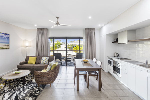 spacious living room with ceiling fan, air conditioning and kitchenette with microwave, oven, toaster and fridge in 1 Bedroom hotel apartment in Broome, Western Australia