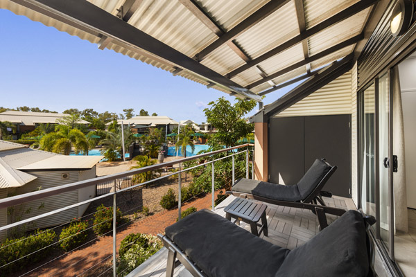 table, chairs and sun loungers in sunshine on large private balcony of Cable Beach Accommodation 1 Bedroom Apartment at Oaks Cable Beach Sanctuary hotel in Broome, Western Australia