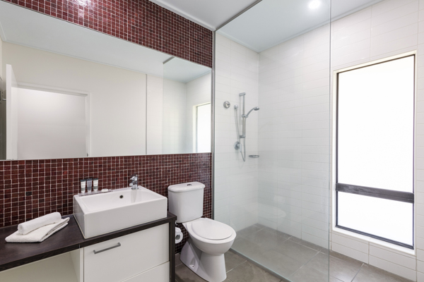 clean en suite bathroom with toilet, mirror and adjustable disabled access shower in air conditioned 2 Bedroom Apartment at Broome hotel, Western Australia