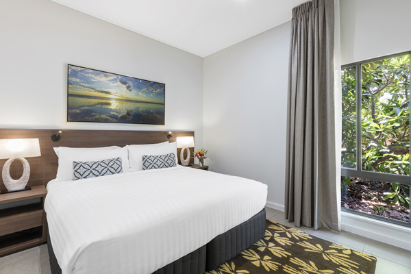 big double bed with clean white sheets and comfortable pillows next to large windows in 3 Bedroom Villa at Oaks Cable Beach Sanctuary hotel in Broome, Western Australia