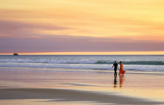 Broome hotels near Cable Beach overlooking ocean with couple walking hand in hand and pink sunset in background