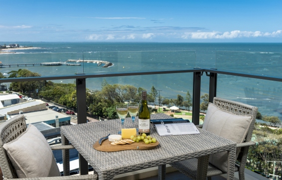 Redcliffe hotel balcony with wine and cheese on table on balcony near beach overlooking ocean with Moreton Bay islands in background and dolphins swimming in the waves, Queensland, Australia