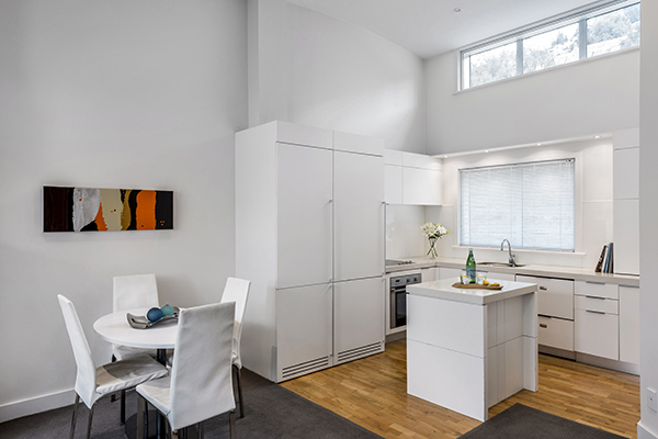 big open plan 2 bedroom hotel apartment living room with desk and office chairs and Wi-Fi for corporate travellers to do work while visiting Queenstown on business trips to New Zealand