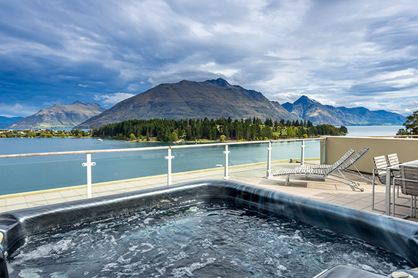 hot tub, spa bath jacuzzi on private balcony of 2 Bedroom Apartment with views of Lake Wakatipu and The Remarkables mountain range at Oaks Club Resort hotel in Queenstown, New Zealand