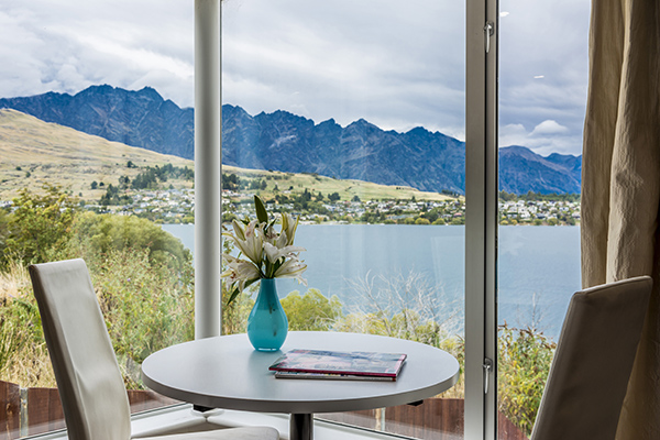table and chairs next to large window of Hotel Room holiday apartment near bungy jumping in Queenstown, New Zealand