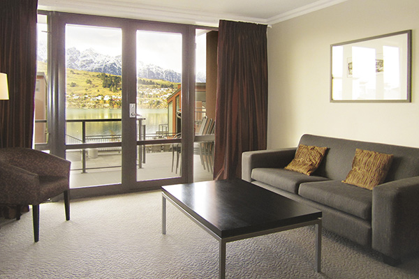 large living room with table and couches next to sliding glass doors leading to sunshine on private balcony outside 2 bedroom holiday apartment at Oaks Shores hotel in Queenstown, New Zealand