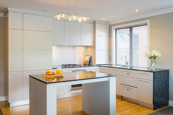 open plan kitchen with bench tops, microwave, stove top hot plates, oven and dishwasher in 2 Bedroom Lake View Apartment at Oaks Shores hotel in Queenstown, New Zealand