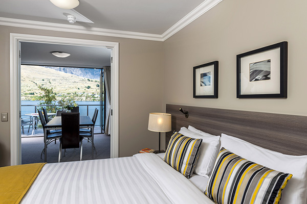 comfortable double bed with clean sheets and big pillows in 3 Bedroom Holiday Apartment with private balcony outside and free Wi-Fi access at Oaks Shores hotel in Queenstown, New Zealand