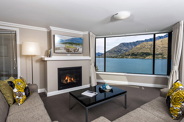 big living room with comfortable couches next to fireplace ideal for family holidays to Queenstown at 4 Bedroom Penthouse holiday accommodation at Oaks Shores hotel