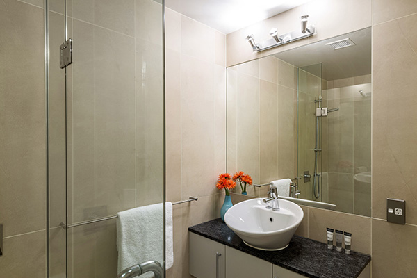en suite bathroom with big mirror, clean towels, toilet and disabled access shower in 4 Bedroom Penthouse holiday apartment at Oaks Shores hotel in Queenstown, New Zealand