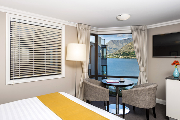 two chairs and table next to comfortable double bed in 4 Bedroom Penthouse holiday apartment with views of Queenstown at Oaks Shores hotel