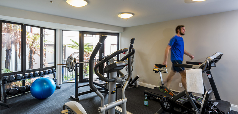 hotel guest using treadmill if fully equipped gym with medicine balls, weights and bench press at Oaks Shores resort in Queenstown, New Zealand