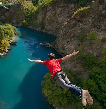 tourist bungy jumping off Kawarau Bridge in Queenstown, New Zealand with tall cliffs either side and blue river below