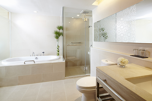 large en suite bathroom with toilet, bathtub, clean towels and big mirrors in 1 Bedroom Apartment suite at Oaks Bangkok Sathorn hotel in Thailand
