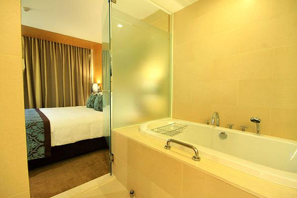 clean en suite bathroom with bath tub, shower, toilet and large mirror in 1 Bedroom Suite at Oaks Bangkok Sathorn hotel in Thailand
