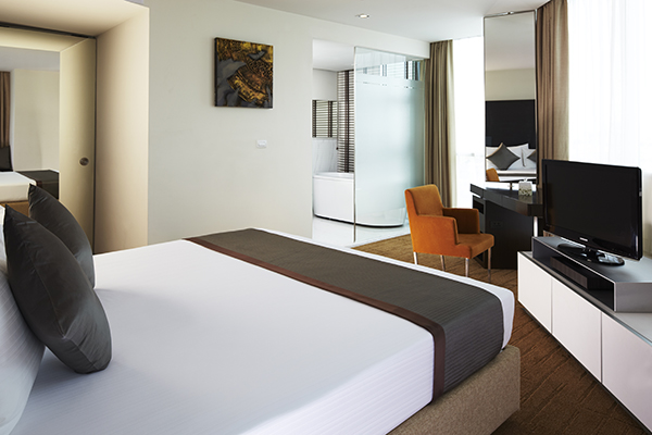 Sathorn hotel Bangkok with comfortable double bed with clean sheets in front of satellite TV in 2 Bedroom holiday apartment with air con and Wi-Fi at Oaks Bangkok Sathorn hotel in Thailand