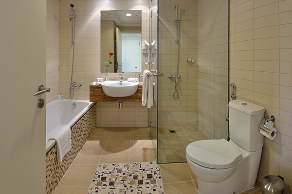 en suite bathroom with bathtub, toilet, shower and clean white towels in Deluxe 1 Bedroom holiday apartment at Oaks Liwa Heights hotel in Dubai, United Arab Emirates